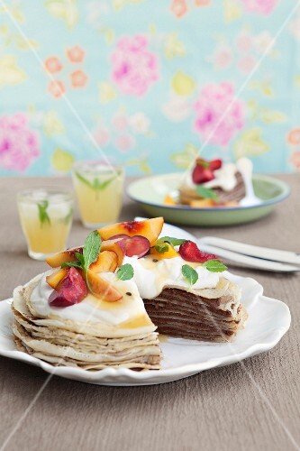 Pancake cake with chocolate cream, salted caramel, peaches, plums and grenadilla