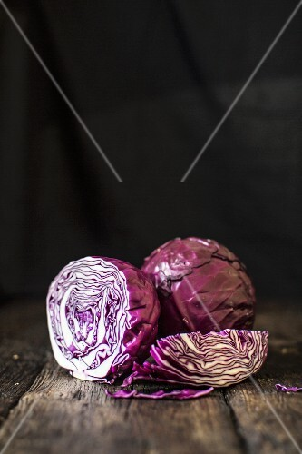 Red cabbage, whole and sliced, on a wooden surface