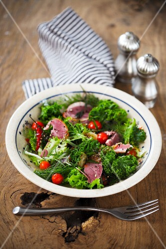 A green kale salad with goose breast and cherry tomatoes