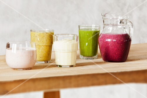 Various smoothies on a wooden table