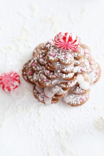 A gingerbread biscuit Christmas tree decorated with icing sugar and peppermint bonbons