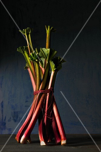 A bunch of rhubarb on a wooden surface against a blue background