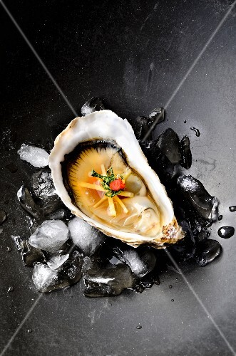 An oyster with ginger, miso and chilli on ice cubes