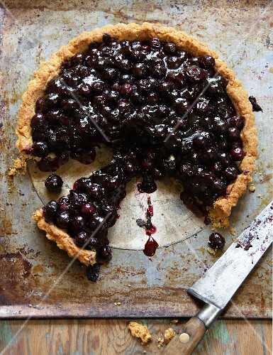 A sliced blueberry and almond tart on an old baking tray with a knife