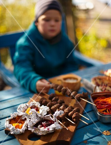 A child with venison skewers at an autumn picnic in a forest