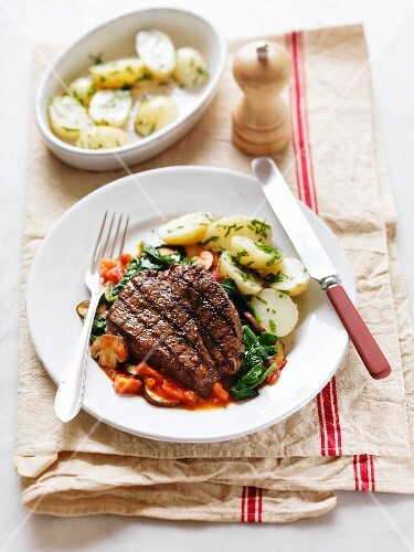 A grilled steak on a bed of vegetables served with herb potatoes