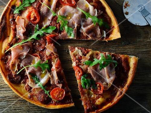 pizza mit prosciutto tomaten und rucola angeschnitten bild kaufen 11287187 stockfood. Black Bedroom Furniture Sets. Home Design Ideas