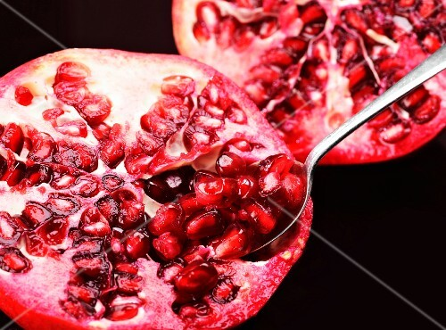 A pomegranate with a spoon