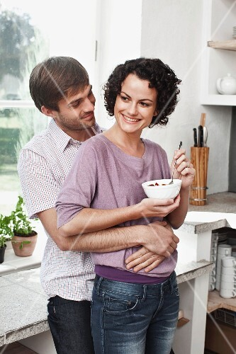 A couple embracing in the kitchen with the woman holding a muesli bowl