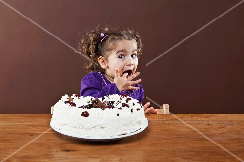 A young girl sneaking a taste of a cream cake