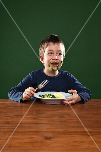 A boy smeared with spinach eating spinach with potatoes