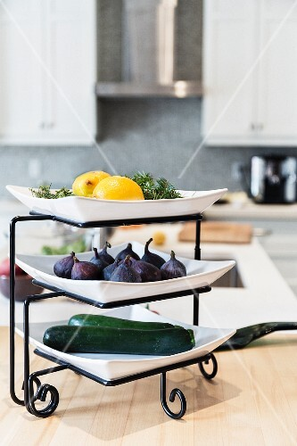 Fresh fruit and vegetables on a plate stand in a kitchen