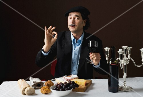 A stereotypical French man with a cheese platter, grapes and red wine