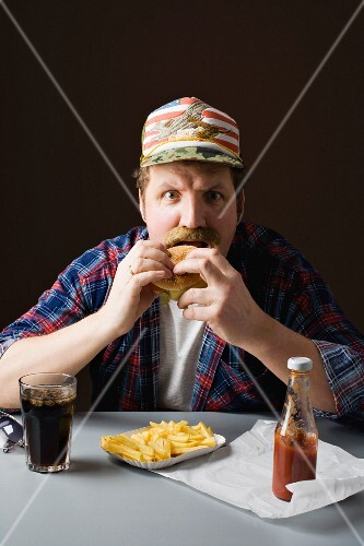 A stereotypical American man eating burger and fries with cola