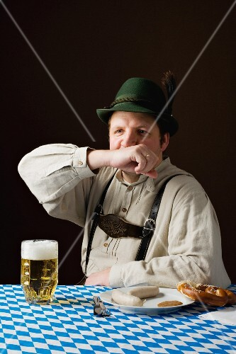 A stereotypical German man wearing lederhosen with beer and white sausage wiping his mouth