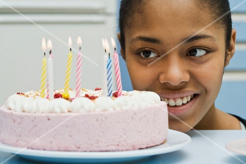 A teenager looking at a birthday cake