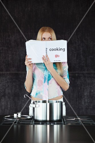 A woman with a cookbook in front of a stove