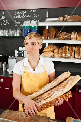 A sales assistant holding a basket of baguettes in a bakery