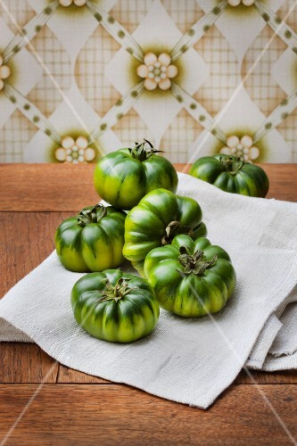 Green tomatoes against retro wallpaper