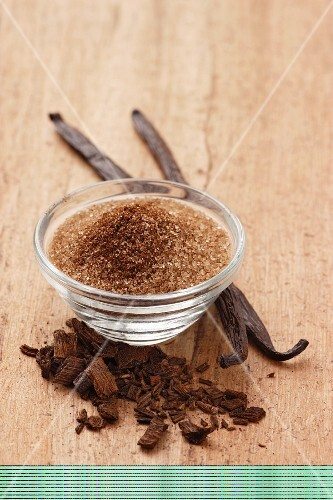 Brown vanilla sugar in a glass bowl with vanilla pods