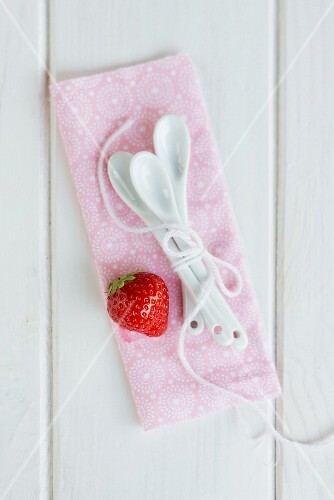 A strawberry and dessert spoons on a pink cloth