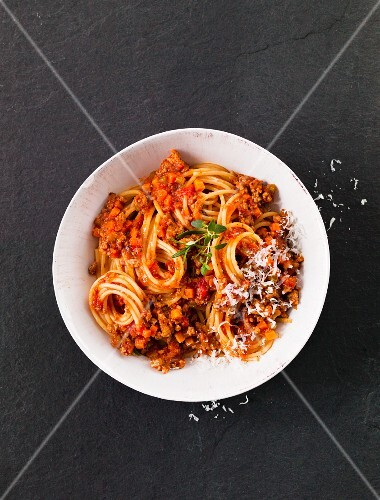 A bowl of spaghetti bolognese on a black surface (seen from above)