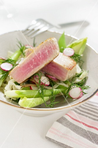 Tuna steak on a bed of salad with radishes and dill