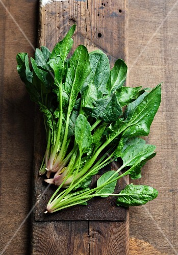 Fresh spinach leaves on a wooden surface