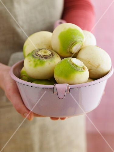 Hands holding a sieve filled with white turnips