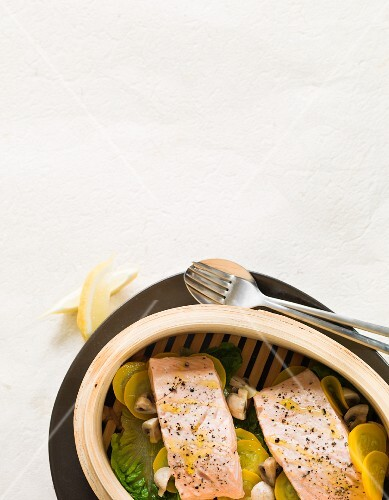 Salmon fillets on vegetables in a steamer basket