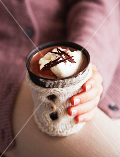 A woman holding a mug of hot chocolate