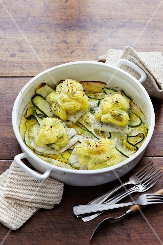 Cod fillets topped with mashed potatoes on a bed of courgettes