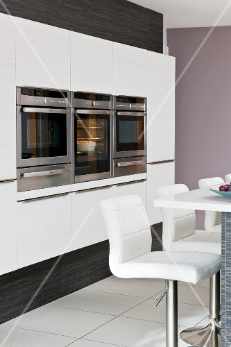 White leather barstools at a bar in front of a built in units housing kitchen devices in a contemporary style