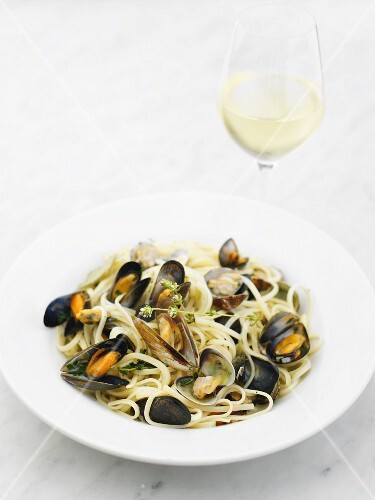 Spaghetti with mussels and clams on a white plate