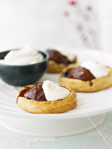 Puff pastry pear tartlets with chocolate sauce and cream