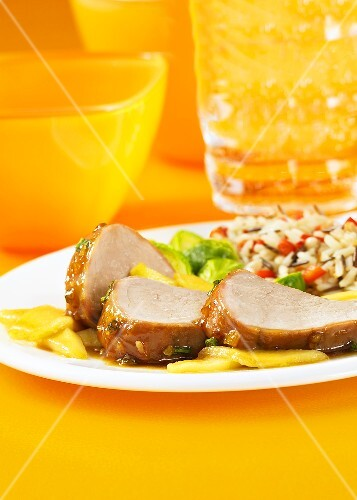 Roast tender loin of pork with glazed apples and rice