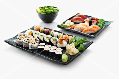 Two sushi platters with wasabi and ginger