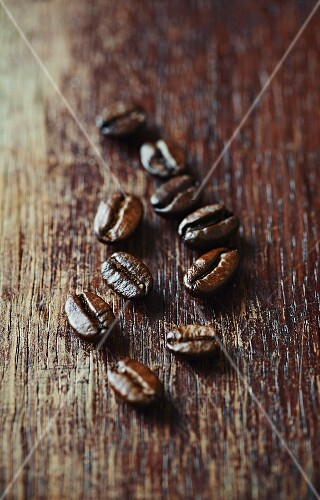 Dark organic coffee beans on a wooden surface