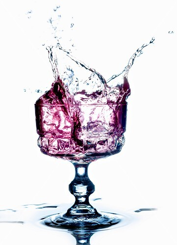 A purple drink splashing from a glass