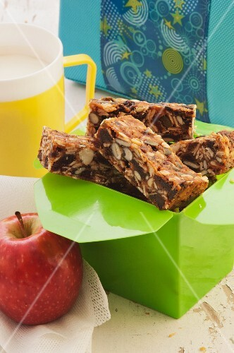 Homemade muesli bars to take away with an apple and a cup of milk