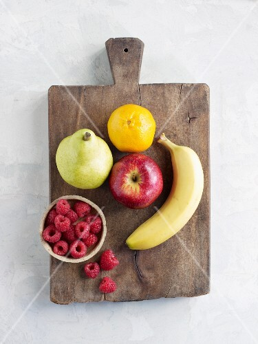 Various types of fruit on a wooden board (seen from above)