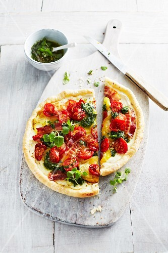 Pizza with pesto, tomatoes, bacon and herbs on a chopping board