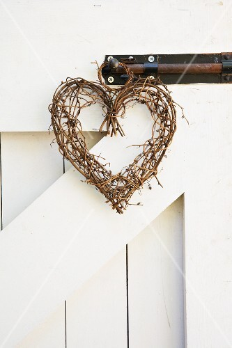 A heart-shaped wreath made from willow twigs hanging from a bolt on a wooden gate