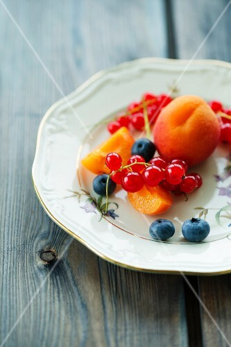 A fruit platter with apricots, blueberries and redcurrants