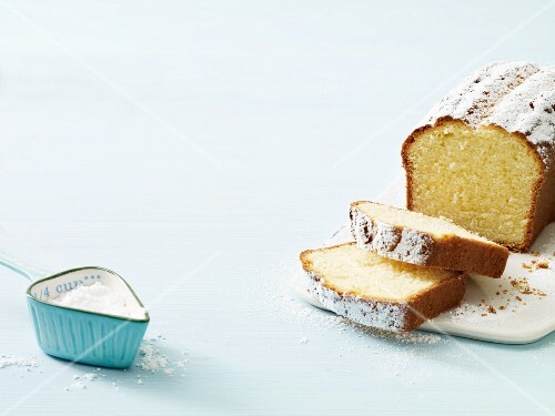 A sliced Madeira cake with icing sugar