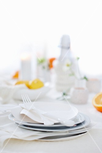 A table laid with white plates and cutlery