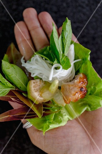 A hand holding a lettuce leaf with pork and rice noodles (loss)