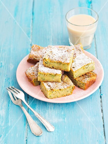 Slices of courgette cake with cinnamon icing sugar