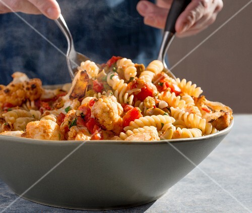 Fusilli pasta being mixed with cauliflower