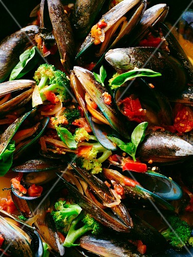 Close up of mussels with broccoli in tomato sauce